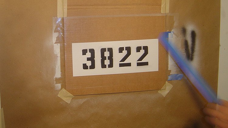 curb address numbers painted on a piece of cardboard.
