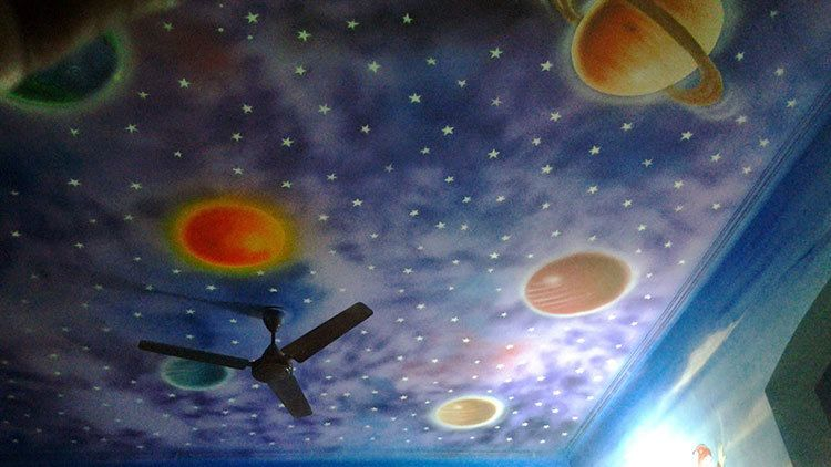 Night sky mural painted on a bedroom ceiling